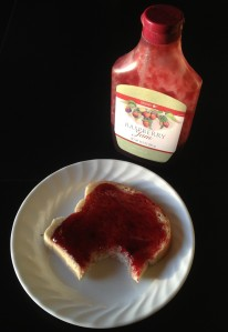 Red raspberry jam on white bread toast on a white plate on a black table